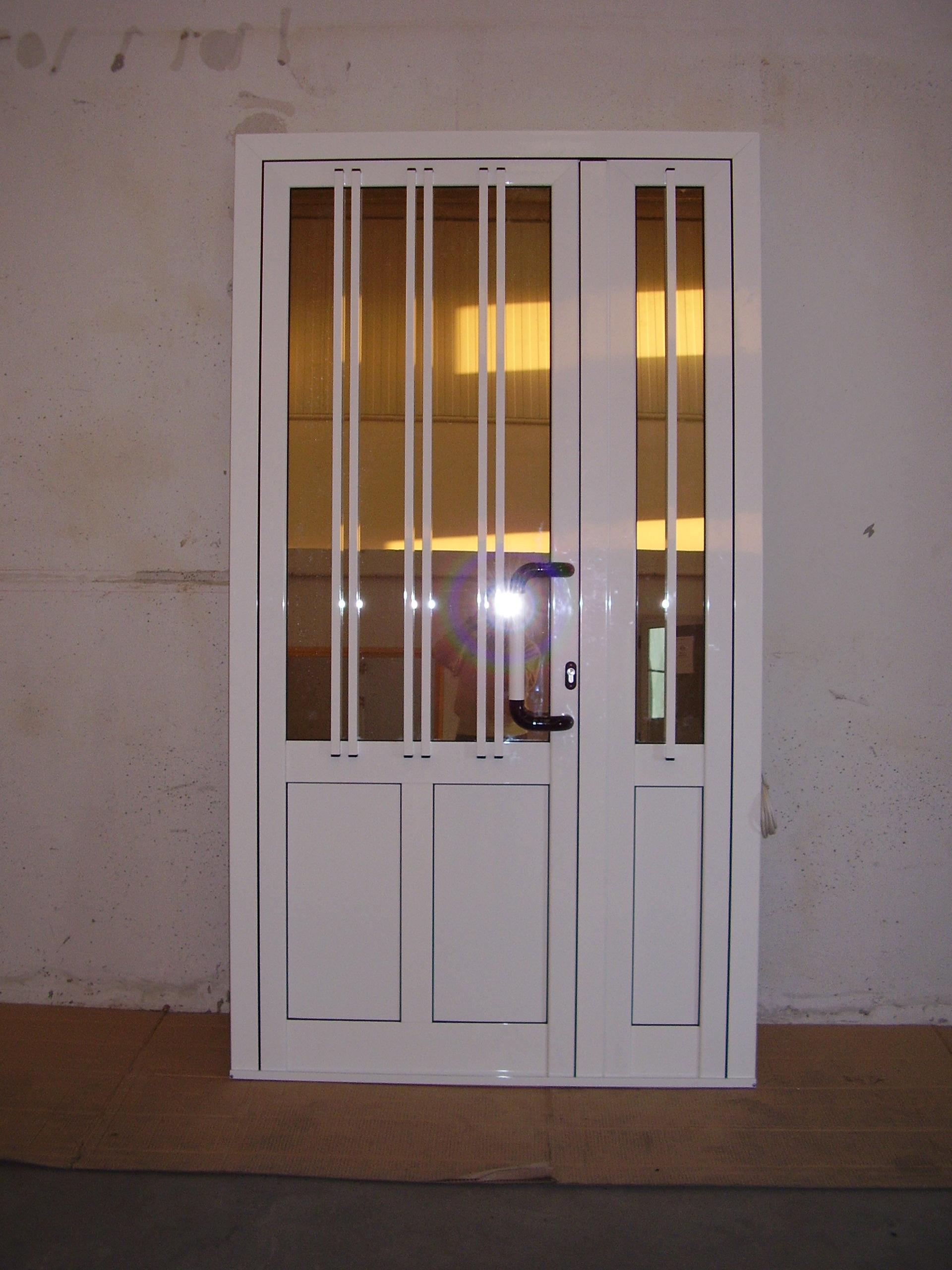 Puerta edificio 2 hojas con entrepaño y cristal